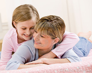 hija-joven-que-abraza-la-madre-mientras-que-miente-en-cama-6581419